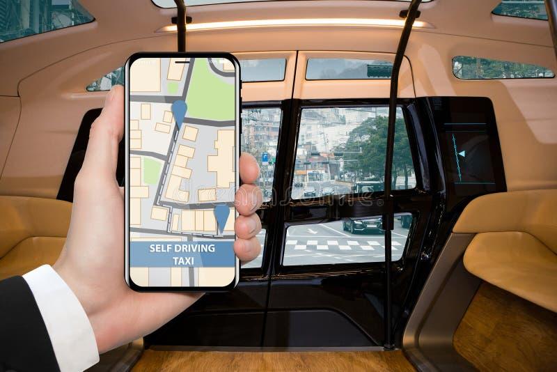 Hand med telefonen på en bakgrund av den autonoma taxien för inreod arkivbild