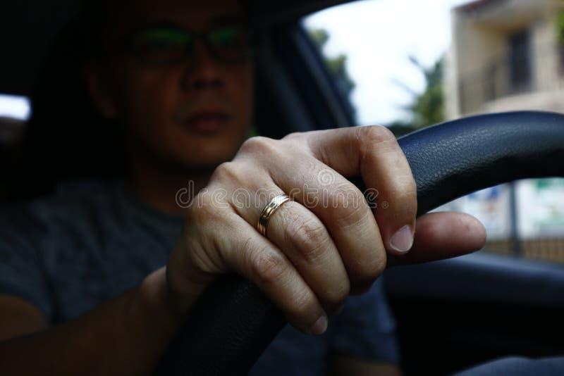 Hand med vigselringen av en asiatisk man inom en bil som rymmer styrhjulet arkivfoton