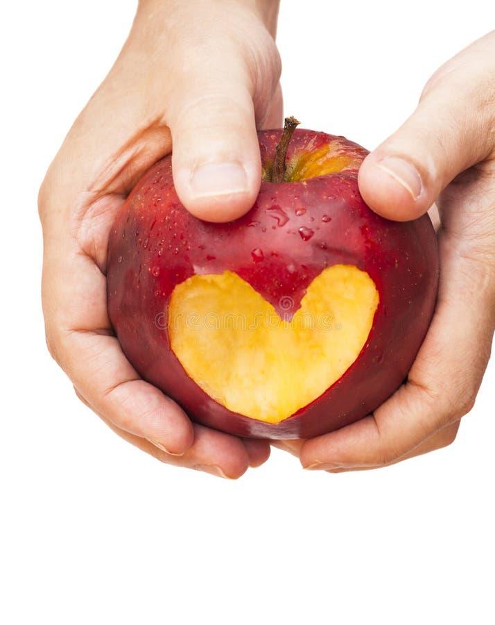 Hand met appel, die een hart snijdt royalty-vrije stock fotografie