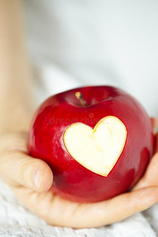 Hand met appel, die hart snijdt royalty-vrije stock foto