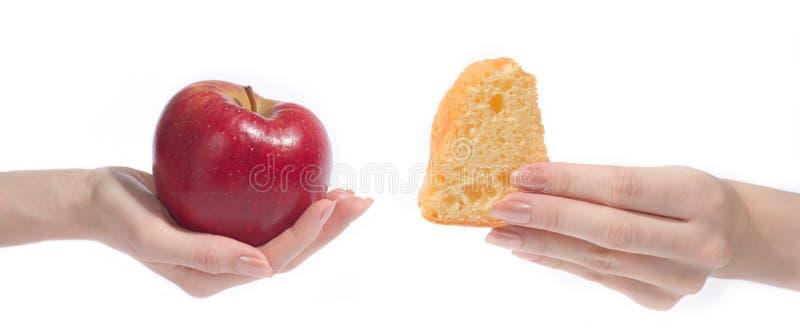 Hand met appel en cake stock foto's