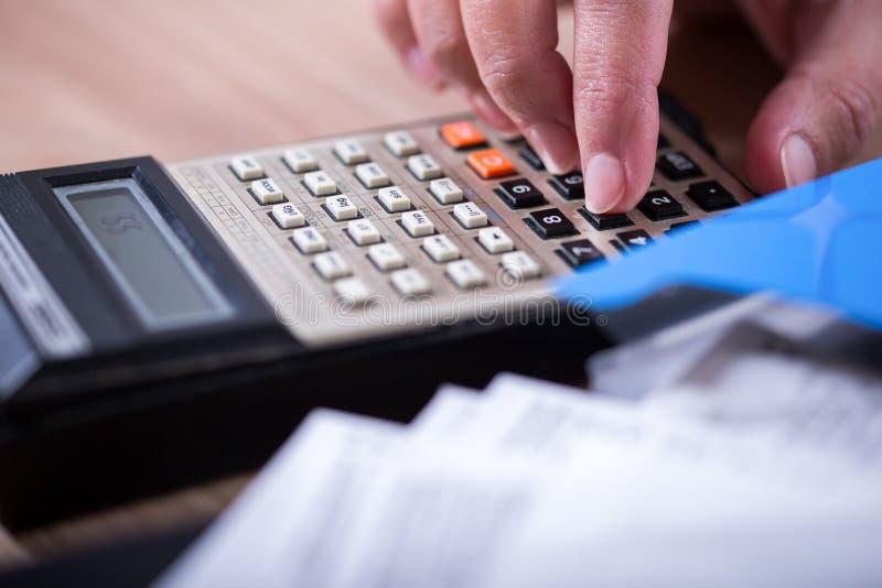 Hand met calculator op document wordt geplaatst dat royalty-vrije stock foto