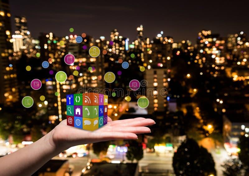 hand met de kubus van toepassingenpictogrammen op het Vage stad bij nacht royalty-vrije stock fotografie