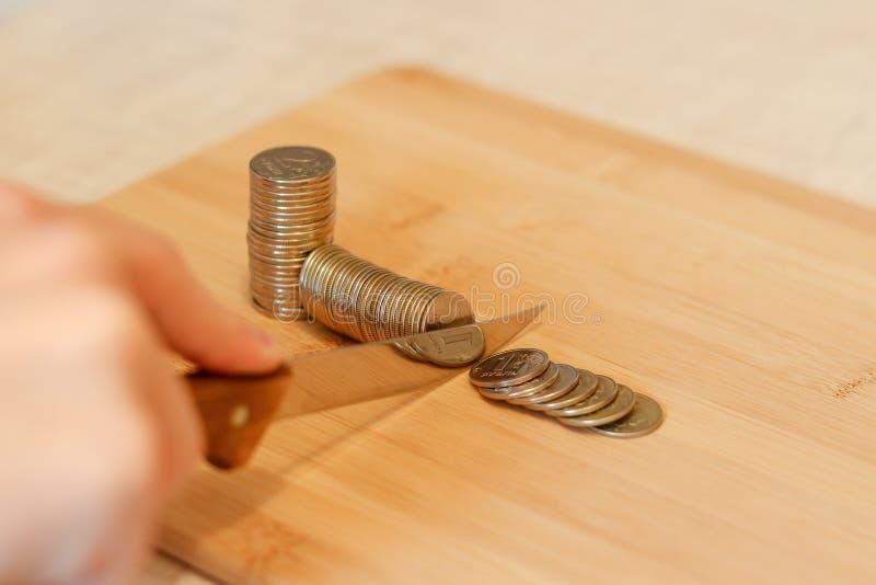 Hand met een mes die een stapel van muntstuk snijden Concept besnoeiingen op de begroting stock afbeeldingen