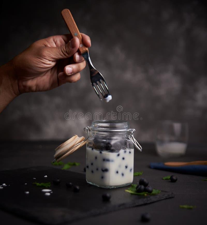 Hand met een vork met een bosbessen met yoghurt stock afbeelding