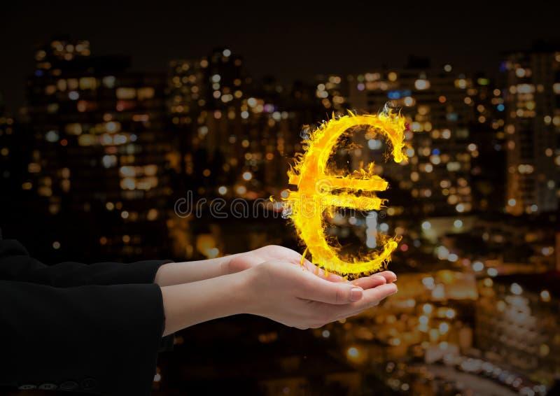 hand met euro brandpictogram over voor de vage stad bij nacht royalty-vrije stock fotografie
