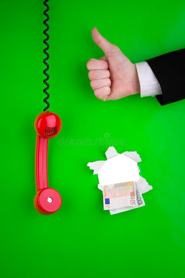 Hand met geld en telefoon stock afbeeldingen