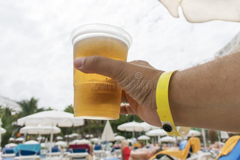 Hand met glas van bier en al inclusieve armband royalty-vrije stock foto's