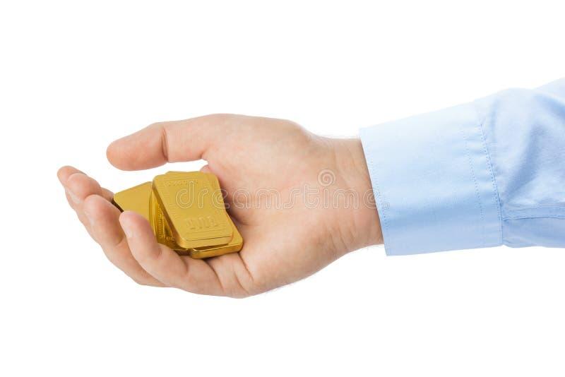 Hand met goudstaven stock foto
