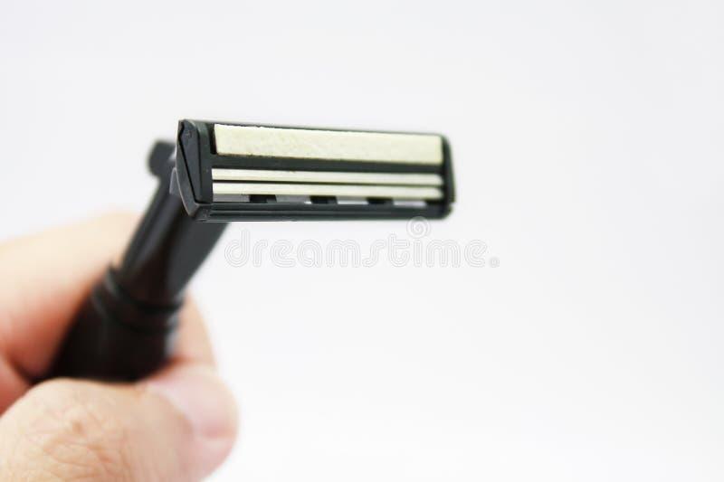 Hand met het scheren van scheermes op een wit stock fotografie