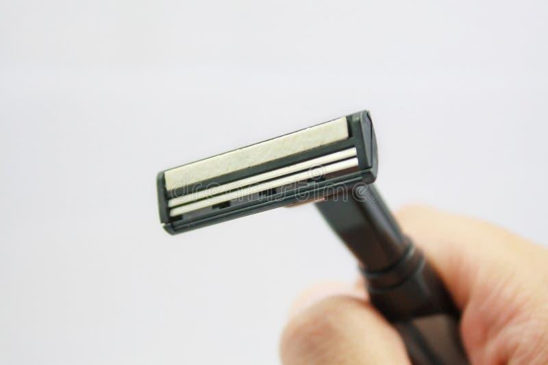 Hand met het scheren van scheermes op een wit wordt geïsoleerd dat stock afbeeldingen