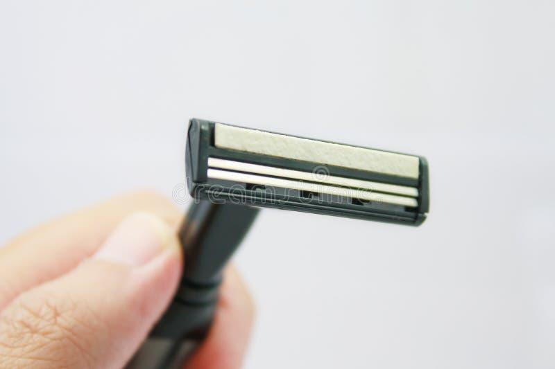 Hand met het scheren van scheermes op een wit wordt geïsoleerd dat royalty-vrije stock foto