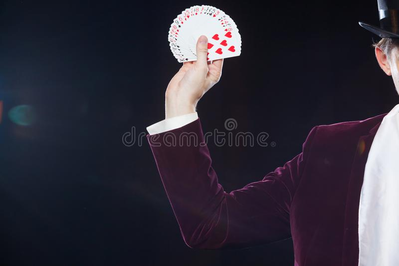 Hand met kaartenclose-up Midsection die van tovenaar gewaaide uit kaarten tonen tegen zwarte achtergrond Tovenaar, Juggler royalty-vrije stock fotografie