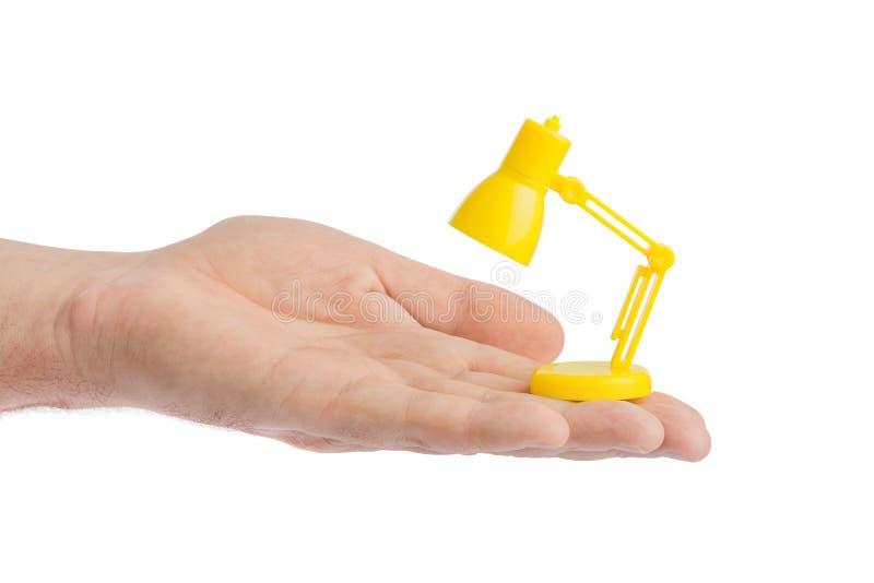 Hand met kleine bureaulamp stock foto
