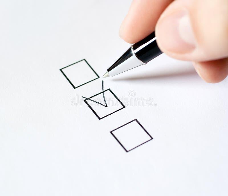 Hand met pen en controledoos, die op witte bac wordt geïsoleerdc royalty-vrije stock foto's