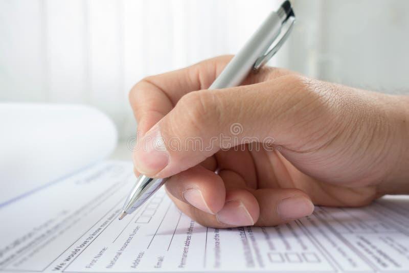 Hand met pen over aanvraagformulier stock foto