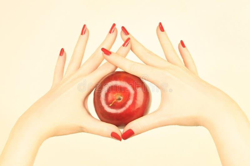 Hand met rode appel stock afbeelding
