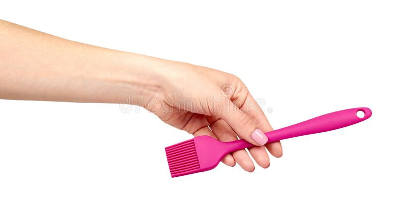 Hand met roze culinaire borstel, keukenwerktuig stock afbeeldingen