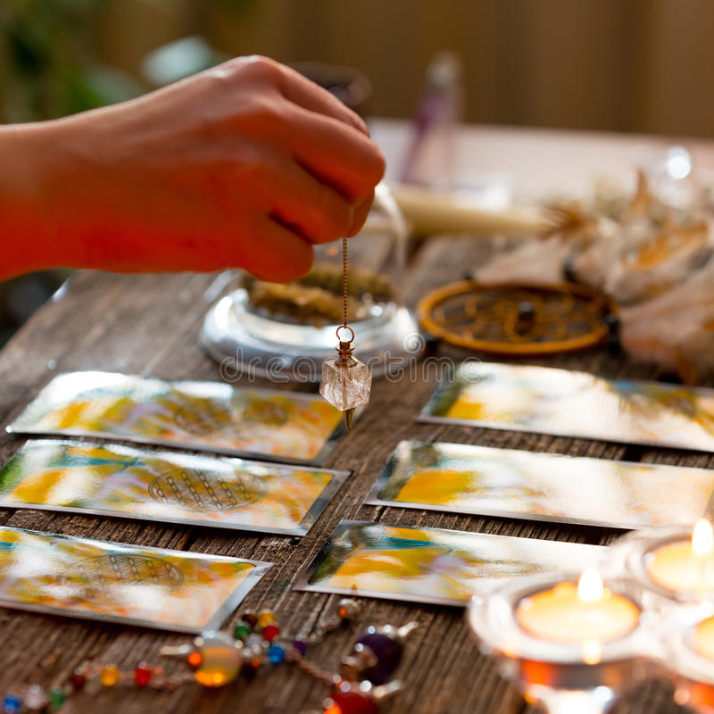 Hand met slinger over tarotkaarten stock foto's