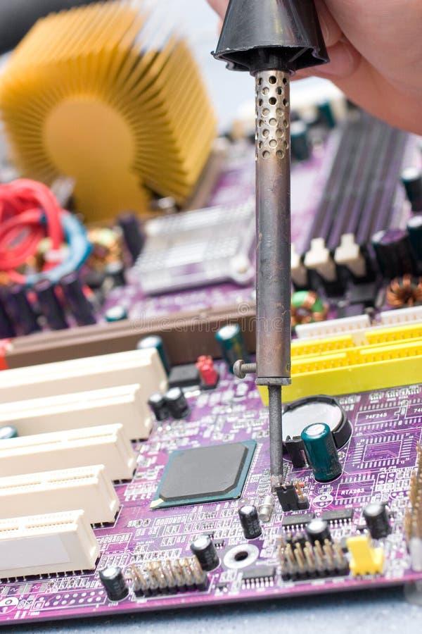 Hand met soldeerbout over motherboard stock foto's