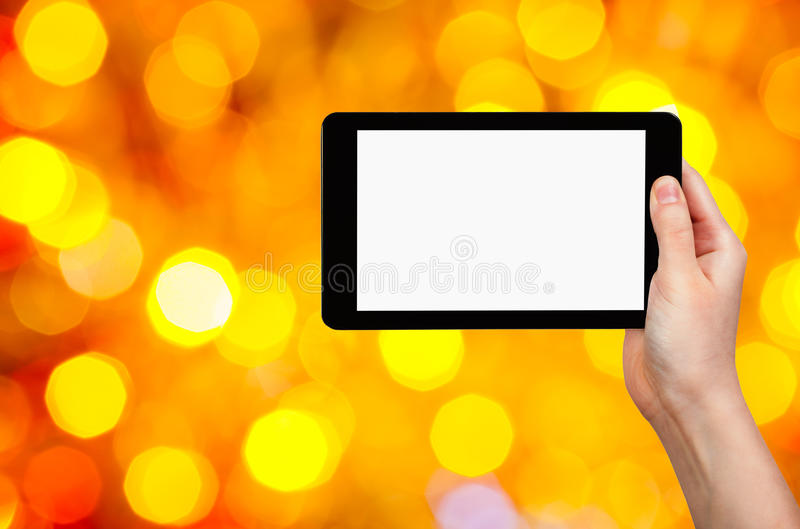 Hand met tabletpc op gele en rode achtergrond stock foto's