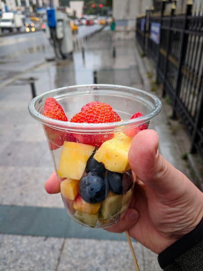Hand met transparante plastic kop gesneden vruchten stock afbeeldingen