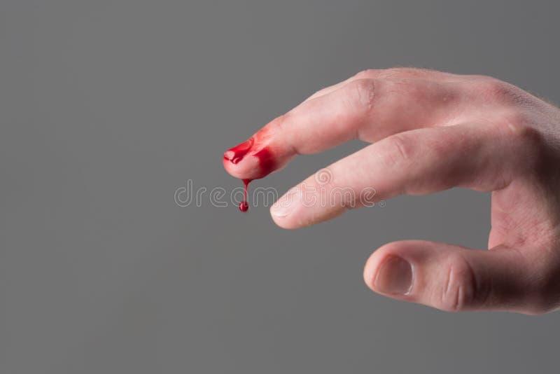 Hand met verwonde bloedige middelvinger grijze achtergrond, exemplaarruimte Schade en verwondingsconcept Druppeltje van bloed het royalty-vrije stock foto's