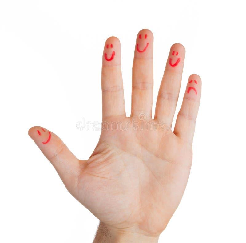 Hand met vingers smileys, behalve één droevige vinger stock afbeelding