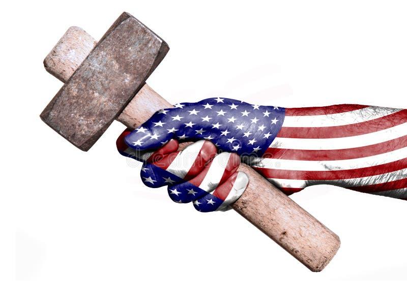 Hand met vlag van Verenigde Staten die een zware hamer behandelen stock foto