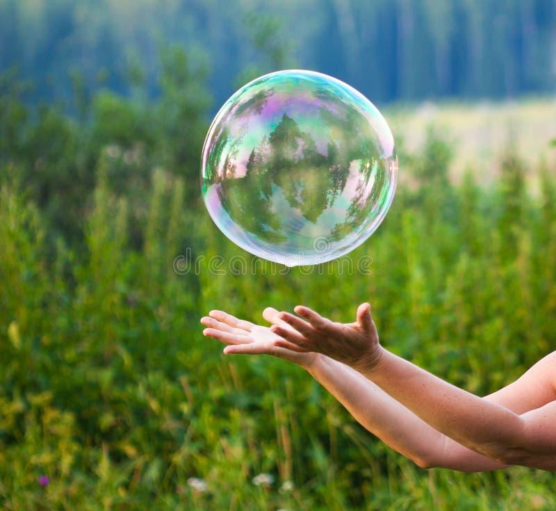 Hand met zeepbel stock foto's