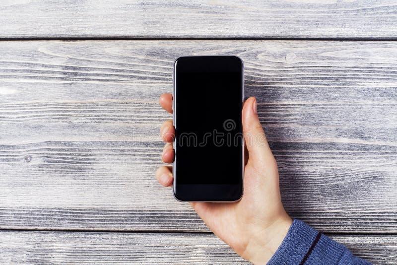 Hand met zwarte smartphone royalty-vrije stock afbeelding