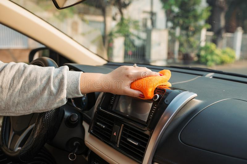 Hand with microfiber cloth cleaning seat, auto detailing and valeting concept, washing car care interior, selective focus.  stock photography