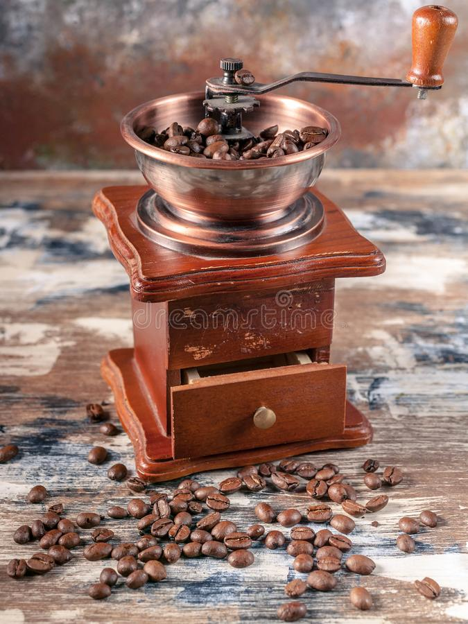 Hand mill or coffee grinder and coffee grains. Vertical shot royalty free stock image