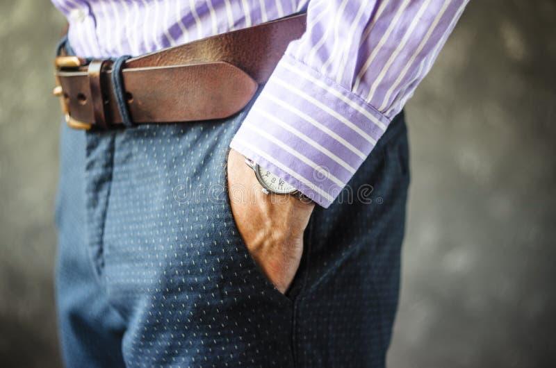 Hand mit Armbanduhr in der Tasche lizenzfreie stockfotos