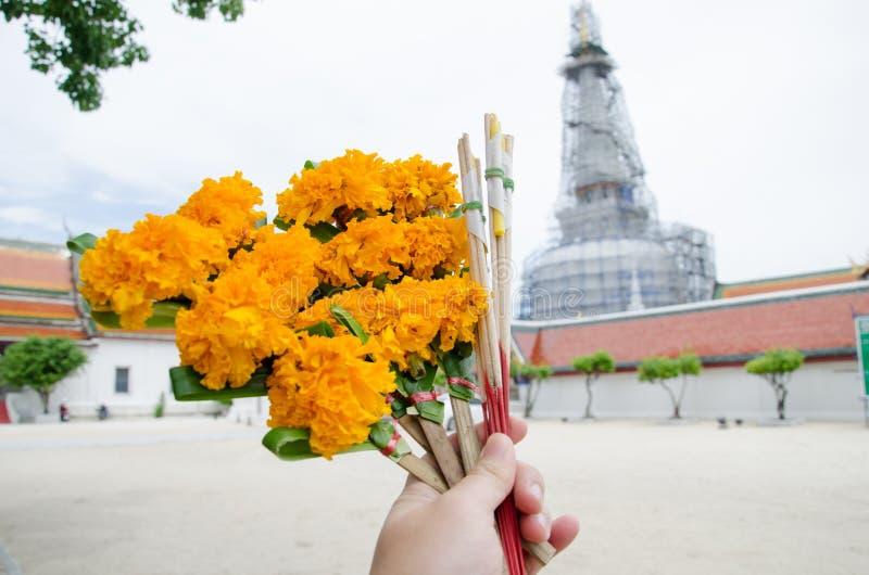 Hand mit Blume, Räucherstäbchen und Kerzen für Anbetung Buddha I stockbild
