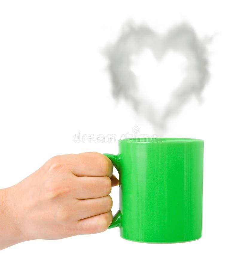 Hand mit Cup und Dampf mögen ein Inneres stockfotografie