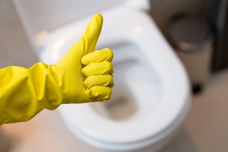 Hand mit dem Handschuh, der Daumen herauf Zeichen gegen saubere Toilette zeigt lizenzfreie stockbilder