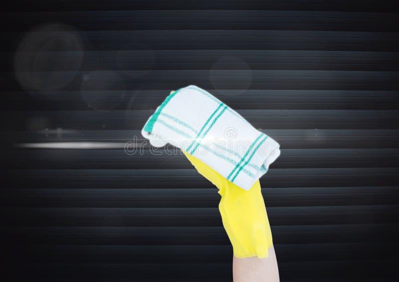 Hand mit dem Lappen, der den Schirm vor Vorhängen säubert stockbild