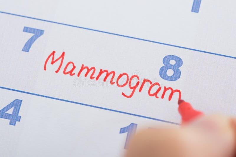 Hand mit dem Mammogramm geschrieben auf Kalender stockfoto