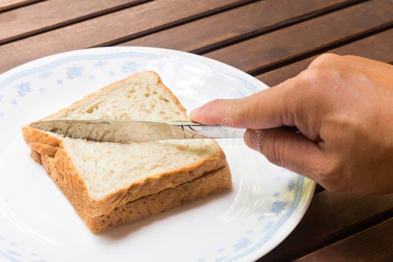 Hand mit dem Messer, das diagonal Vollkornsandwichbrot in zwei Teile schneidet stockfotografie