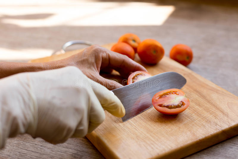 Hand mit dem Messer, das frische rote Tomaten an auf Schneidebrett schneidet stockbilder