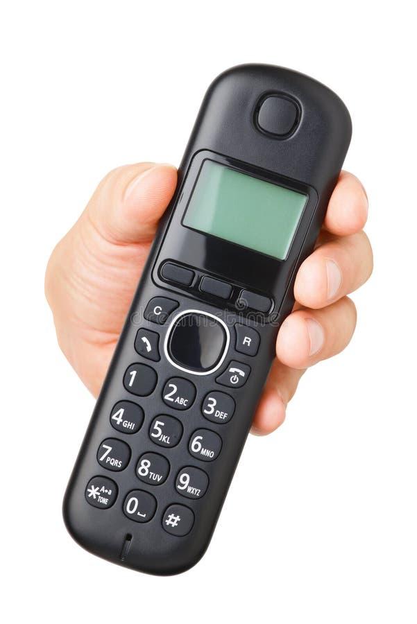 Hand mit dem schwarzen schnurlosen Telefon lokalisiert lizenzfreies stockbild
