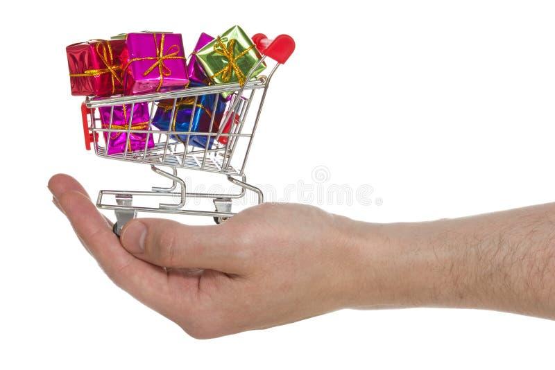 Hand mit dem Warenkorb voll von den bunten Geschenken stockfotografie