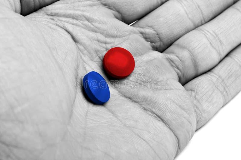 Hand mit den blauen und roten Pillen lizenzfreie stockfotos