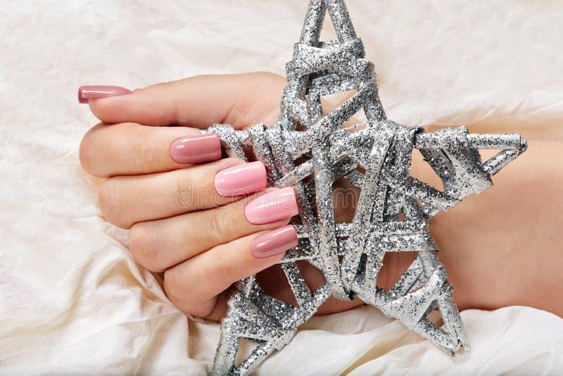 Hand mit den langen künstlichen rosa manikürten Nägeln, die ein silbernes Stern Weihnachtsspielzeug halten stockfotografie