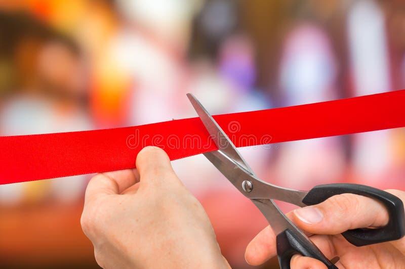 Hand mit den Scheren, die rotes Band - Eröffnungsfeier schneiden stockfoto
