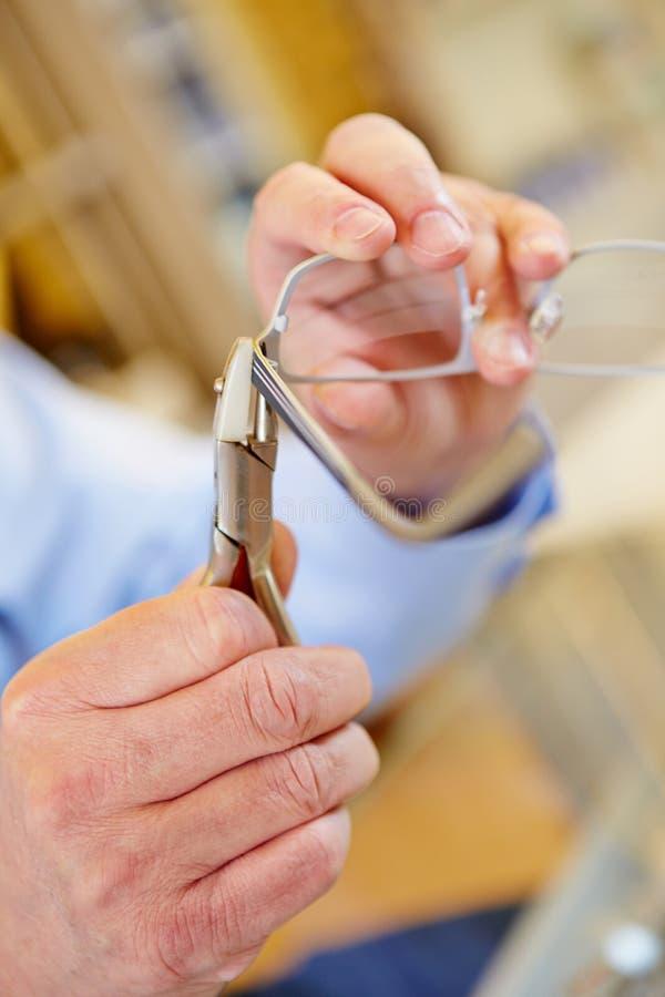 Hand mit den Zangen, die Gläser reparing sind lizenzfreie stockfotografie