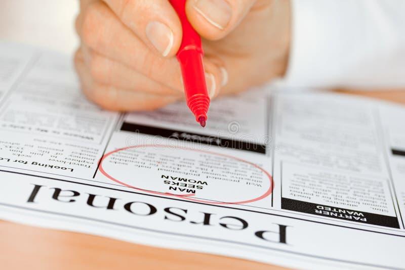 Hand mit der roten Feder, die persönliche in der Zeitung überprüft stockbilder