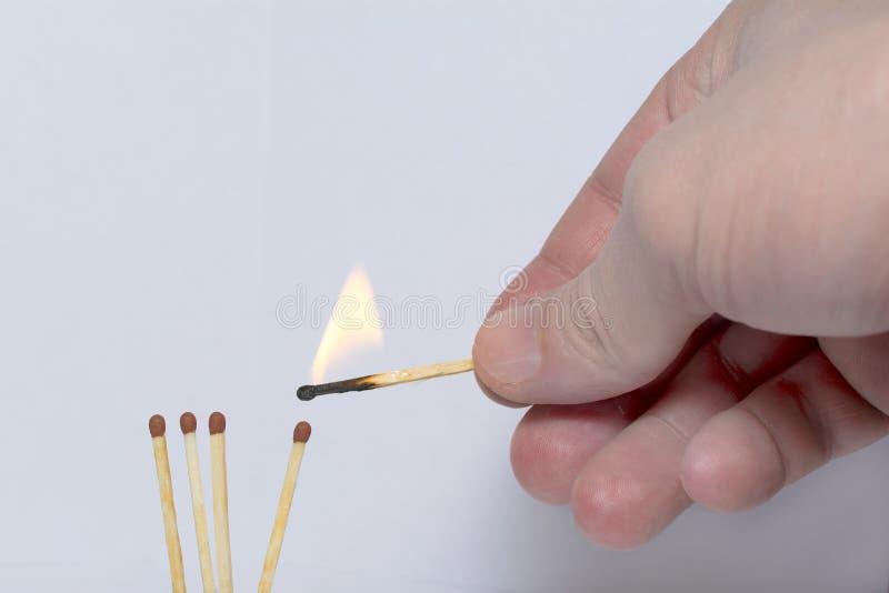 Hand mit einem brennenden Zündholz zündet Match an lizenzfreies stockbild