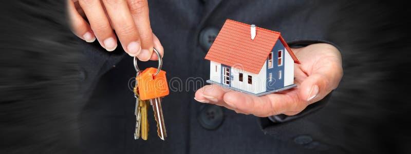 Hand mit einem kleinen Haus und Schlüsseln lizenzfreie stockfotos